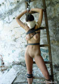 Sexy naked blindfoldet girl roped up against a ladder in a cave