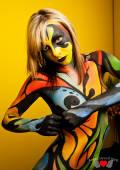 Bodypainted Kayden Love posing in front of yellow wall2.