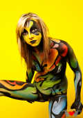 Bodypainted Kayden Love posing in front of yellow wall6.