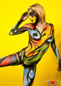 Bodypainted Kayden Love posing in front of yellow wall9.