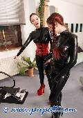 ponygirl and mistress dressed in red and black latex 3