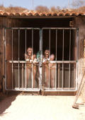 Prision girls in working camp loked up behind ironbars.