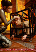 Woman in a cage gets hard punishment from lesbian Domina.