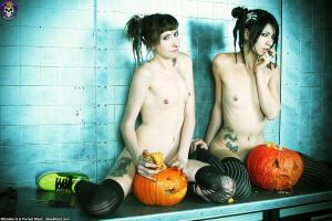 Skinny gothic sluts carving pumpkins on a table