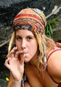 cute hippie girl with dreadlocks stops for a smoke at the beach