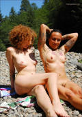 Two natural naked alternative hippis girls playing on the river