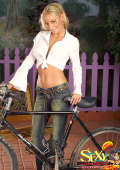 Blonde bicycle girl in denim jeans