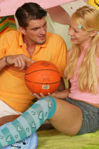 Cute blonde girl posing with basketball trainer