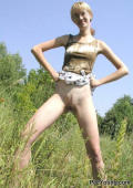 Hot blonde gets wild and pees outdoors in a green field.