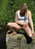 Tempting blonde pees near river.
