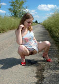 Girl in heels squats on country road.