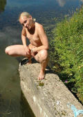 Nude blonde pees in a river