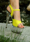 Girl in yellow heels outddor posing.